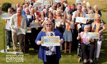 Liz Campbell and other lucky European Postcode Millions winners in Troon celebrating with their cheques