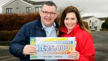 Gavin Connor of Carluke and Judie McCourt stand with Gavin's £25,000 cheque
