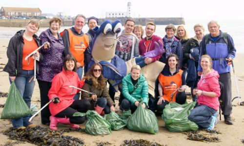 A group of Marine Conservation Society volunteers celebrate a successful day of cleaning