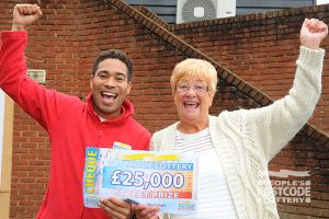01. Maldon player Jennifer Benham being handed her £25,000 cheque by People's Postcode Lottery ambassador Danyl Johnson