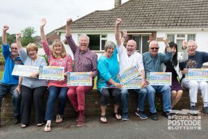 Lucky Torquay Postcode Millions winners celebrating with their cheques