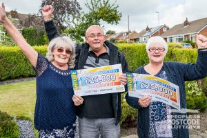 Pleased neighbours John, Val and Susan with their winning cheques