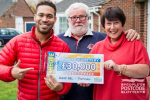 Lynda and her husband Malcolm receiving their £30,000 cheque from Danyl Johnson