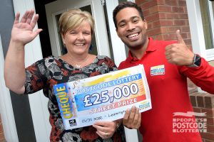 Christine at her doorstep with Street Prize Presenter Danyl Johnson and her winning cheque