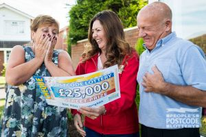 Judie surprising winner Raymond and his wife with their £25,000 cheque