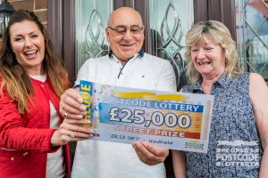 Surprised winners Bernard and Mary receiving their £25,000 cheque