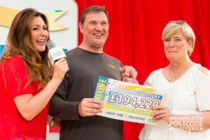 Judie with big winner Chris and his wife Shona, and their £194,229 cheque
