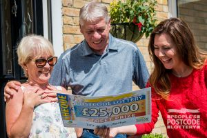 Lucky winner David and his wife being presented with their £25,000 cheque