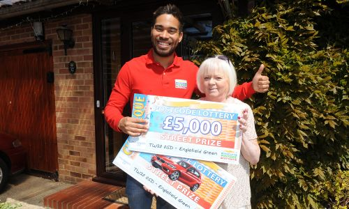 Jennifer Mitchell of Englefield Green showing off her winnings with People's Postcode Lottery Ambassador Danyl Johnson