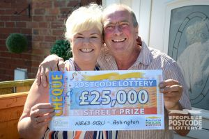 Happy winner Dawn with her partner Peter and their amazing £25,000 cheque