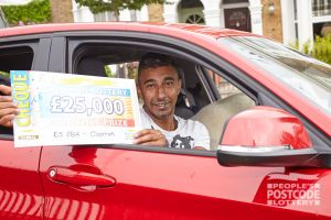 Jaspal sitting in his new car with a £25,000 cheque to boot!