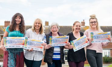 Lucky Exeter winners in the street with their £30,000 cheques