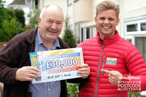 Street Prize Presenter Jeff delivering a big cheque to John