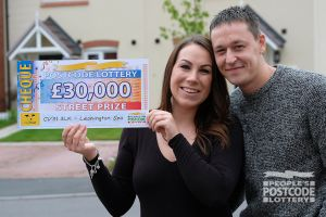 Gemma and Matt showing off their whopping £30,000 cheque