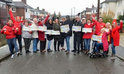The big Stoke-on-Trent winners celebrating in the street with People's Postcode Lottery Ambassadors