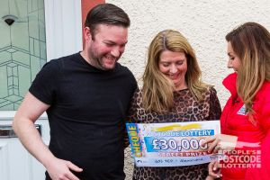 Nicola and husband Stephen looking very pleased as Judie McCourt reveals their £30,000 cheque