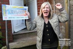 Elizabeth celebrating with the £30,000 cheque