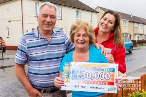 Judie McCourt with winner Pat and her husband John holding their £30,000 cheque