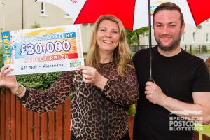 Nicola and husband Stephen holding her £30,000 cheque