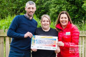 Judie McCourt with winner Tracy and husband Robert holding their £30,000 cheque