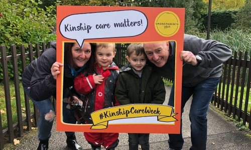 A man and woman, accompanied by two children, with a Grandparents Plus #KinshipCareWeek photo frame