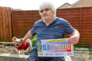 Our winner Andy, joined by Yorkshire Terrier Aidan, with his £30,000 cheque