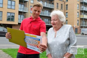 Sheila looking surprised as Jeff Brazier reveals her £30,000 cheque