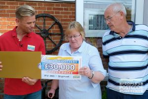 Our Street Prize Presenter Jeff Brazier unveils Elaine's amazing cheque as her husband David looks on