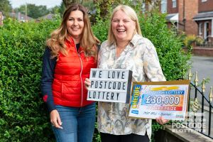 Judie with Karen holding a 'We Love Postcode Lottery' sign and her big cheque