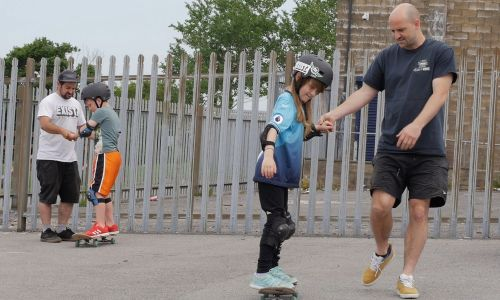 Coaches teach young people how to skate at a CUSP Swansea skate park