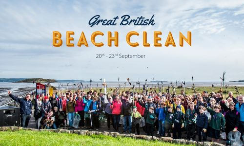 Volunteers at a Marine Conservation Society Great British Beach Clean event hold their pickers aloft