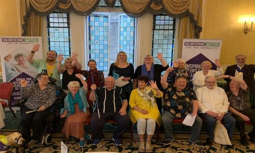 Service users and volunteers at Volunteering Matters show their support to players of People's Postcode Lottery