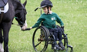 A young boy in a wheelchair wearing an RDA jumper and riding helmet feeding a horse