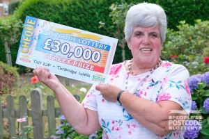 Lucky neighbour Patricia holding her amazing cheque