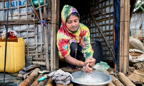 Hafeza cleaning her hands at the doorstep of her tent during the COVID 19 outbreak in the Rohingya Refugee Camp in Cox's Bazar, Bangladesh