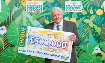 Sir David Attenborough with a £500,000 cheque for Fauna & Flora International