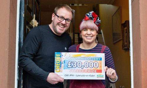 One of our delighted Warwick-on-Eden winners, Caroline and partner Paul, with their lucky cheque