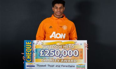 Postcode Hero Marcus Rashford MBE with a £250,000 cheque, raised by our players, for the Trussell Trust and FareShare